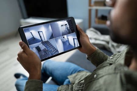 Persona que supervisa las cámaras Vista en vivo de la casa en la tableta digital Foto de archivo