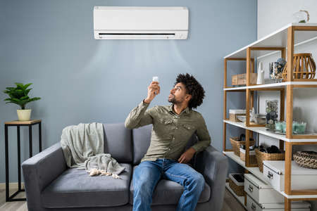 Young Happy Man Sitting On Couch Operating Air Conditioner With Remote Control At Home