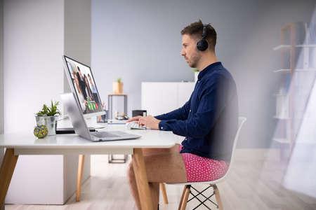 Joven empresario con auriculares durante videoconferencia en computadora Foto de archivo