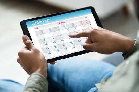 Cropped Image Of Young Man Using Calendar On Digital Tablet At Home