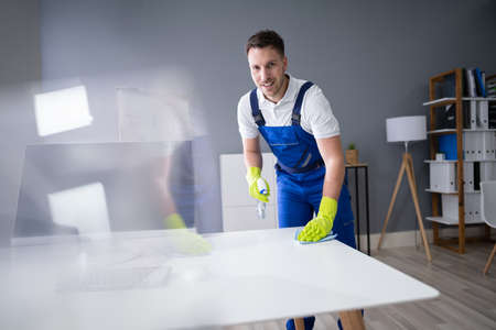 Portrait Of Happy Young Maid Cleaning Glass Table In Office Foto de archivo - 134609888