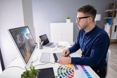 Rear View Of A Man Working On 3D Landscape On Computer In Office Foto de archivo - 134609891