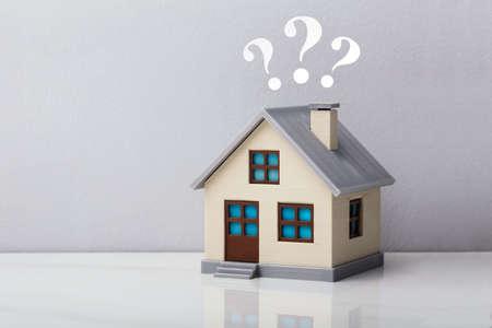 Modelo de casa pequeña con signos de interrogación sobre escritorio reflectante contra un fondo gris