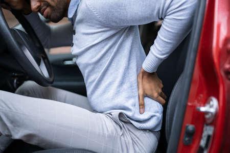 Conducteur debout ayant des maux de dos après avoir conduit une voiture