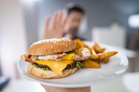 Close-up de la mano de un hombre rechazando la hamburguesa ofrecida por persona