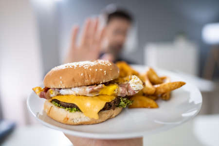 Close-up Of A Man's Hand Refusing Burger Offered By Person
