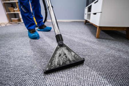 Nahaufnahme eines Reinigungsteppichs mit Staubsauger