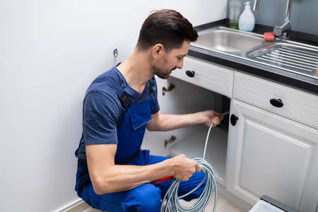 Male Plumber Cleaning Clogged Sink Pipe In Kitchen Standard-Bild