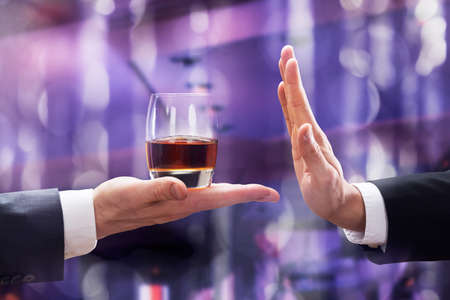 Close-up Of Businessman Hand Rejecting Glass Of Whiskey Offered By Businessperson Against Illuminated Background