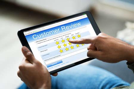 Close-up van persoon op de bank met digitale tablet met enquêteformulier Stockfoto