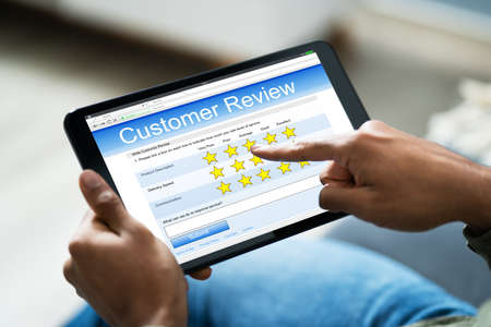 Nahaufnahme einer Person auf dem Sofa mit digitalem Tablet mit Umfrageformular Standard-Bild