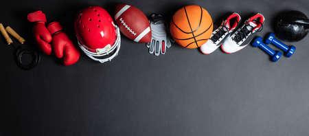 Panoramablick auf verschiedene Sportbälle und Ausrüstung über schwarze Oberfläche