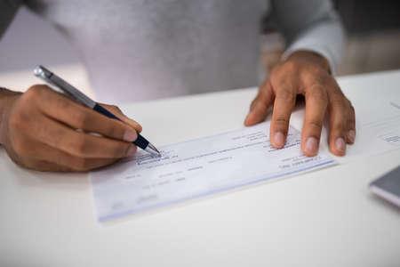 Close-up van de hand van een ondernemer die de check-in op kantoor ondertekent
