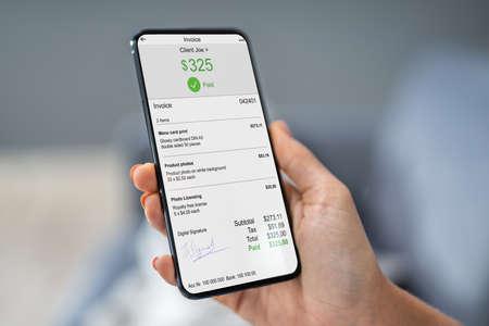 Nahaufnahme der Geschäftsperson mit Laptop beim Bezahlen der Rechnung auf dem Handy im Büro