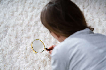 Young Female Looking At Carpet With Magnifying Glass