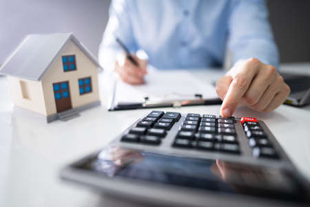 Close-up Of A Person Hand Calculating A Real Estate Property Tax On Wooden Desk Фото со стока
