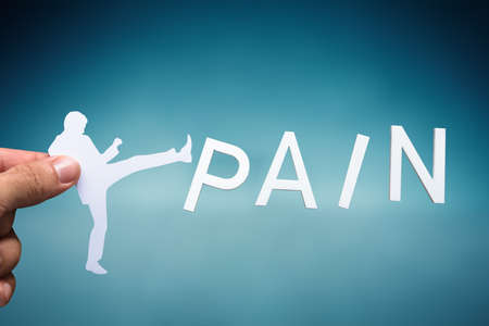Human Hand Holding White Cut Out Human Figure Kicking White Pain Word On Blue Backdrop