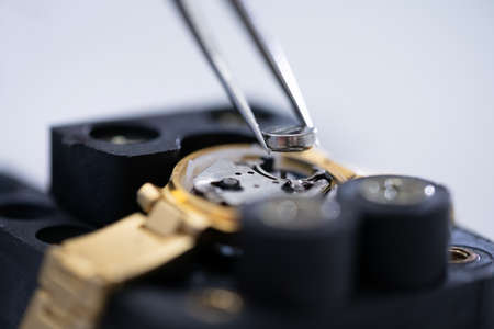 Close-up Of Tweezers Placing Battery On Golden Wrist Watch 版權商用圖片