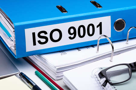 Close-up Of An Office Desk With Iso 9001 Folder And Other Office Supplies