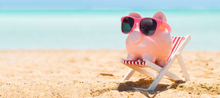 Pink Piggybank Wearing Eyeglasses On Deck Chair Over The Sandy Beach