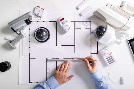 Close-up Of An Architect's Hand Drawing Blueprint With Security Equipment On Desk