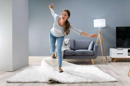 Photo de femme trébuchant avec un tapis dans le salon à la maison Banque d'images