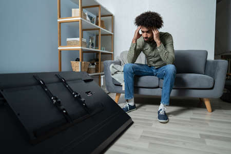 Man Sitting On Sofa In Front Fallen Television With Broken Screen Stock Photo