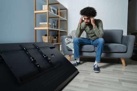 Mann sitzt auf Sofa vor gefallenem Fernseher mit zerbrochenem Bildschirm Standard-Bild