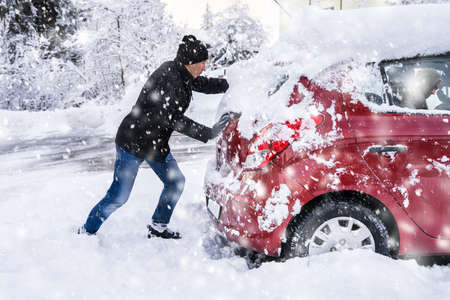 Man Pushing A Car Stuck In The Snow After Heavy Snowfall
