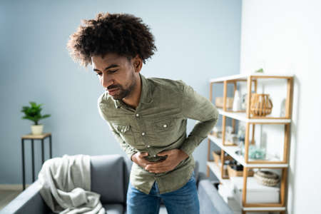 Midsection Of Man With Stomach Ache Standing Near Couch At Home