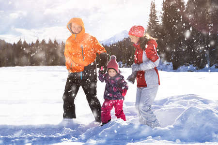 Happy Father And Mother With Their Daughter Playing In The Snow At Laax Archivio Fotografico - 137446655