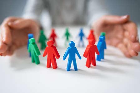 Close-up of a Person's Hand protégeant les pions multicolores formant un cercle sur un bureau blanc Banque d'images
