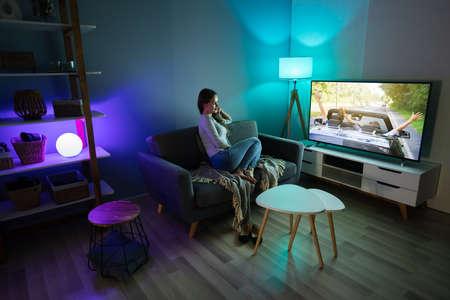Giovane donna seduta sul tappeto a guardare un film in televisione a casa