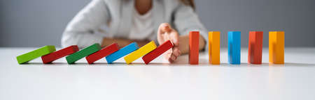 High Angle View Of A Businessperson Stopping Colorful Dominoes From Falling On Desk Stockfoto