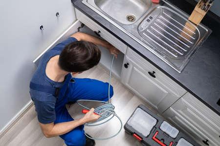 Plombier mâle nettoyage évier tuyau obstrué dans la cuisine