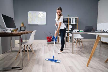 Volledige lengte van vrouwelijke conciërge die de vloer in kantoor dweilt