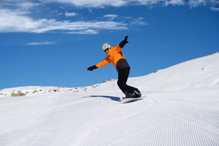 Happy Young Male Snow Boarder Enjoying Riding Snow Board On Track Against Snowcapped Mountains