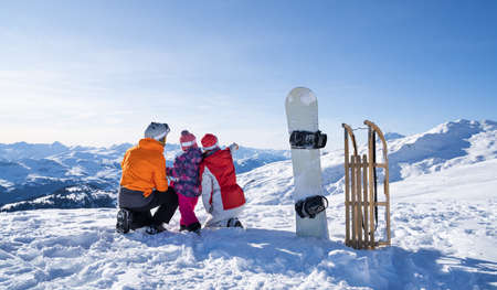 Showing Something To Their Cute Little Daughter By Pointing Near Snowboard And Sledge Stock Photo - 137365886
