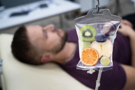 Hombre en el hospital recibiendo infusión intravenosa de rodajas de fruta dentro de una bolsa de solución salina Foto de archivo