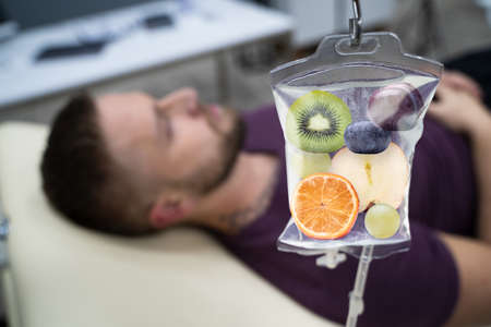 Uomo in ospedale che riceve un'infusione endovenosa di fette di frutta all'interno della sacca di soluzione fisiologica Archivio Fotografico