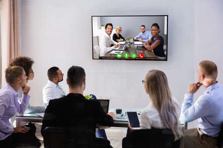 Group Of Smiling Business People Having Video Conference Meeting With Their Colleagues At Office