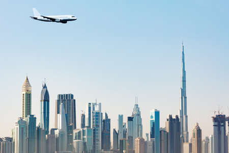 Commercial Airplane Flying Over Modern Dubai Skyscrapers Against Clear Blue Sky