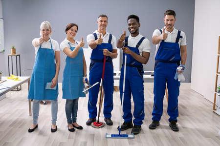 Portrait von glücklichen verschiedenen Hausmeistern im Büro mit Reinigungsgeräten mit Daumen hoch