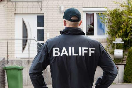 Achteraanzicht van een mannelijke deurwaarder die met zijn handen op de heupen bij de ingang van het huis staat