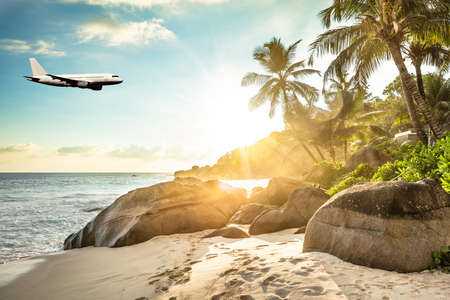 Airplane Is Flying In Cloudy Sky Over Island And Sea In Summer At Seychelles