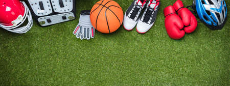Panoramic View Of Various Sports Accessories Over Fake Green Turf Grass Background