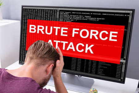 Sider View Of An Upset Businessman Looking At Computer Screen With Brute Force Attack Message