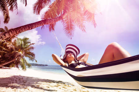 Close-up Of A Young Woman Relaxing On Hammock Over The Sandy Beach Near Palm Tree Archivio Fotografico - 137939202