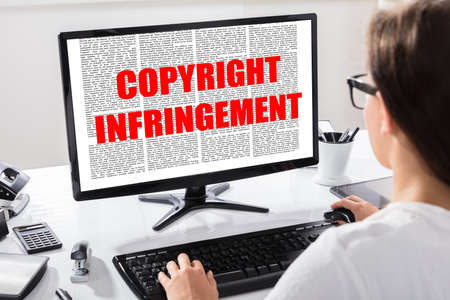 Rear View Of A Young Woman Reading Agreement With Copyright Infringement Text Over Computer Screen