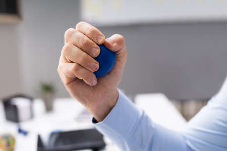 Close-up Of Person Hand Holding Blue Stressball Imagens